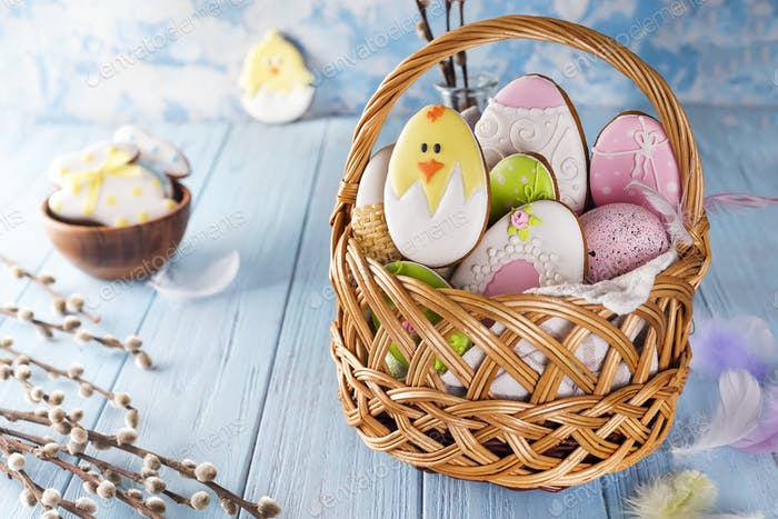 Decorated Easter Cookies in wooden basket on a blue wooden background