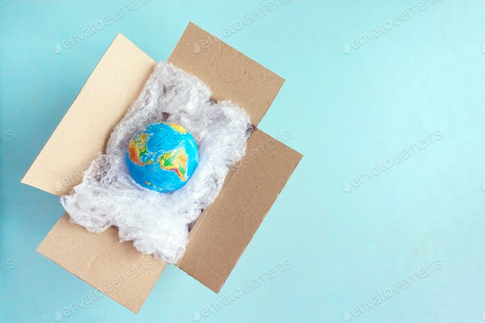 Physical globe, Earth in plastic wrap in carton box on blue background with copy space Recyclable