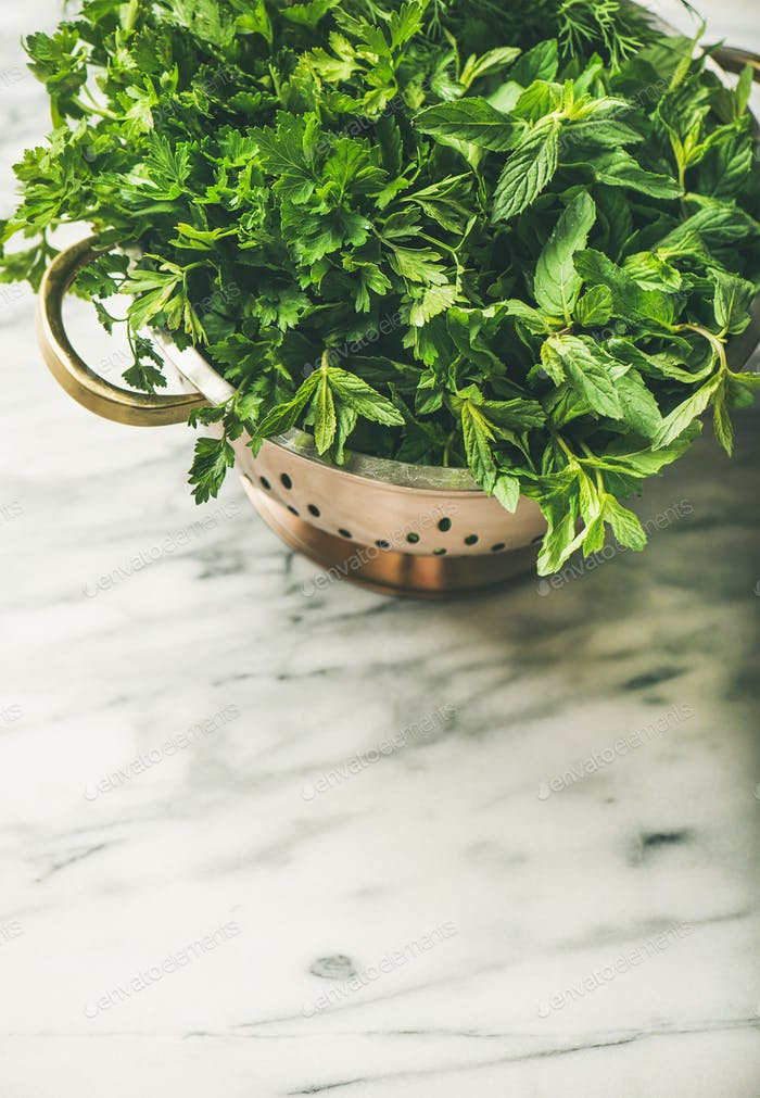 Bunch of fresh green garden herbs in brass colander