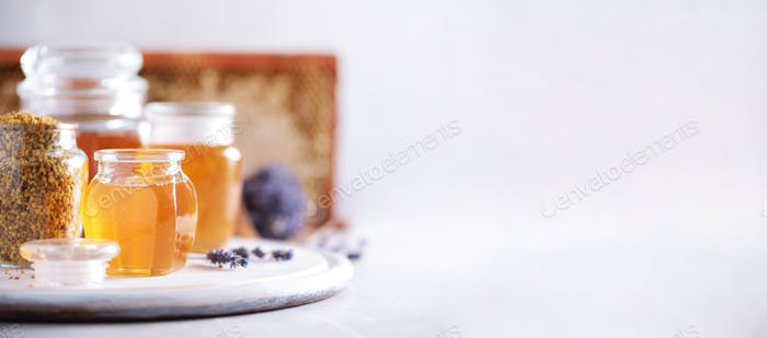 Honey products background. Honeycomb frame, bee pollen granules, honey in glass pot on grey concrete