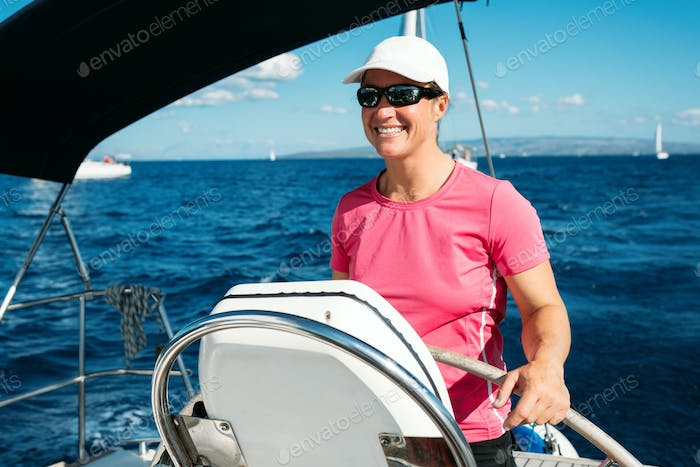 Happy strong woman sailing with her boat