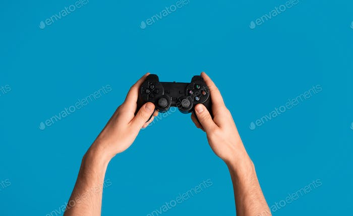 Young man holding videogame joystick on blue background, closeup of hands