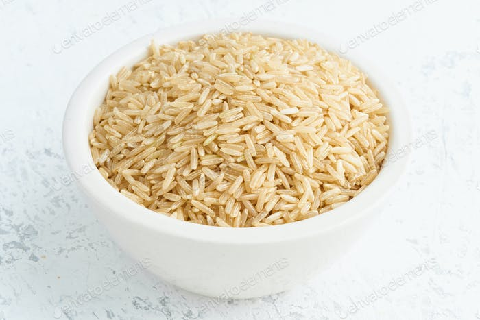 Brown rice in white bowl on white background. Dried cereals in cup,