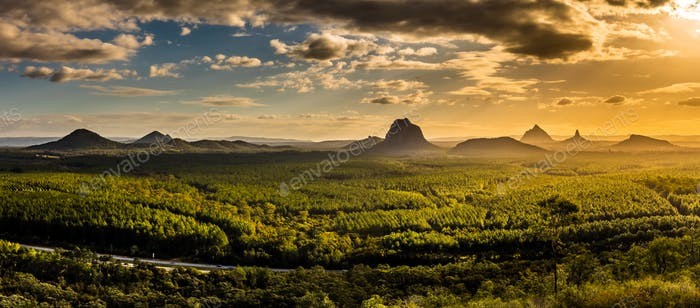 Panoramic view of Glass House Mountains at sunset visible from W