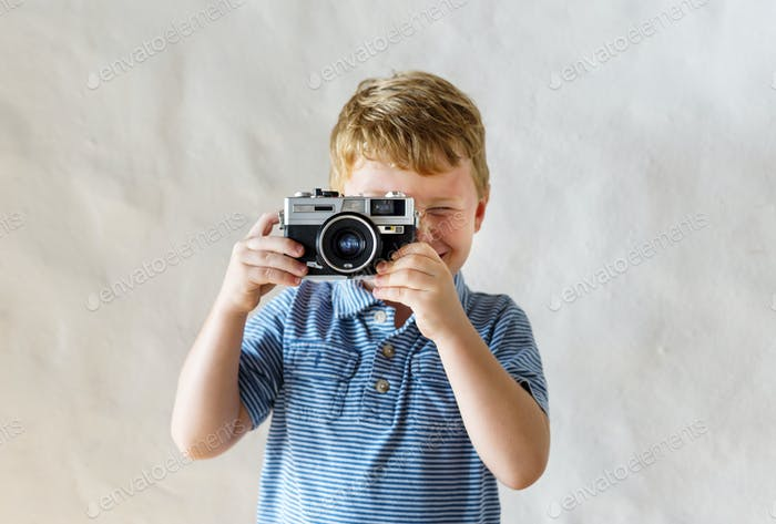 Caucasian boy playing with a camera