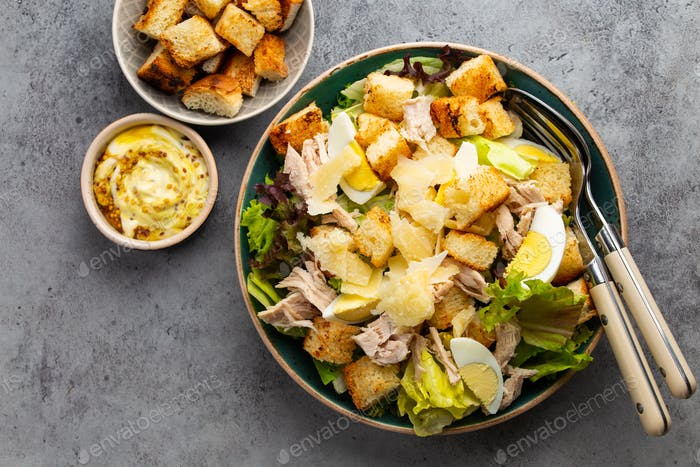 Fresh Caesar salad with lettuce salad, chicken breast, boiled eggs and croutons in ceramic bowl