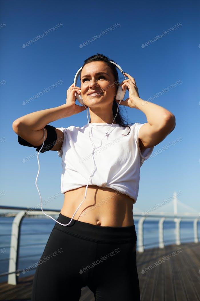 Happy woman in headphones preparing for outdoor training