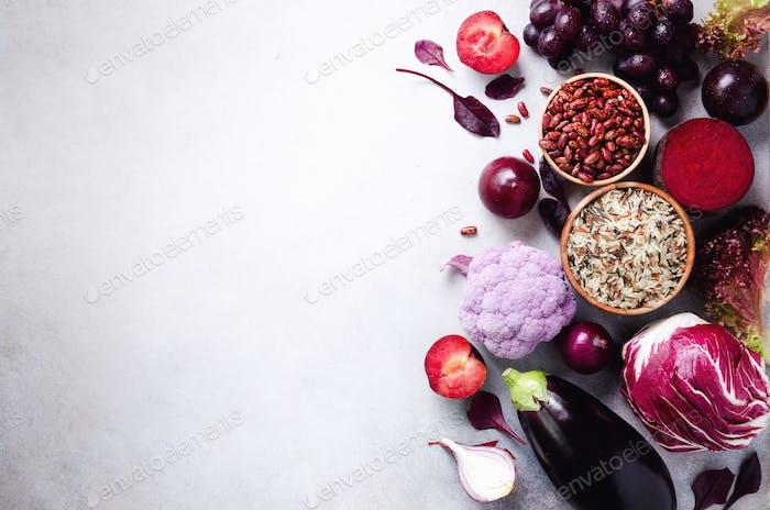 Purple vegetables, fruits on grey background. Violet eggplant, beets, cauliflower, purple beans
