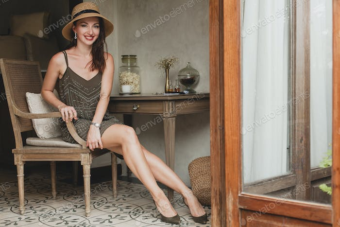 young beautiful stylish woman in resort hotel room, sitting at table