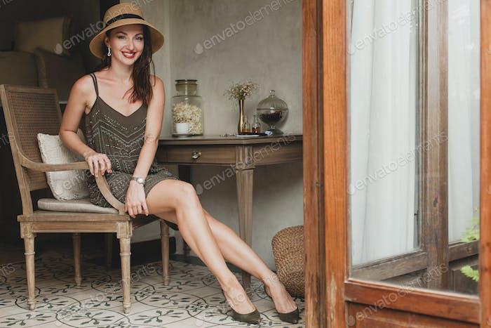 joven hermosa mujer elegante en la habitación del hotel resort, sentado en la mesa