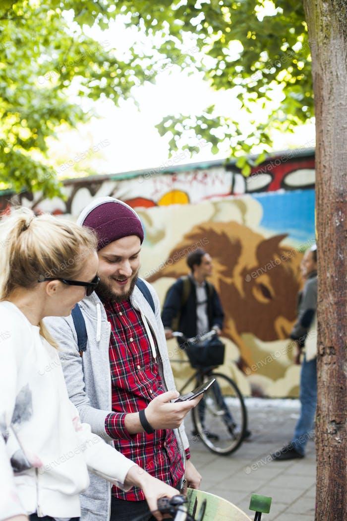 Freunde mit Smartphone auf Bürgersteig