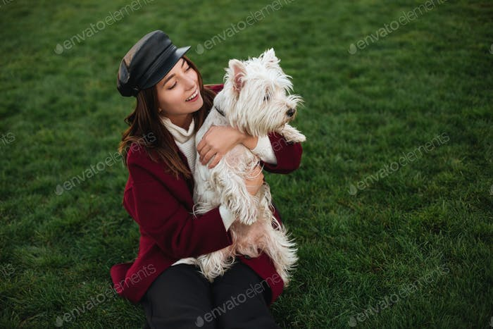 Young beautiful lady in black cap and coat sitting in park and holding in hands her small cute dog