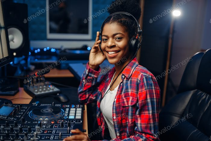 Female musician in headphones in recording studio