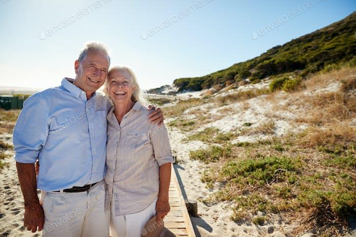 Senior white couple standing on a beach embracing and smiling to camera, three quarter length