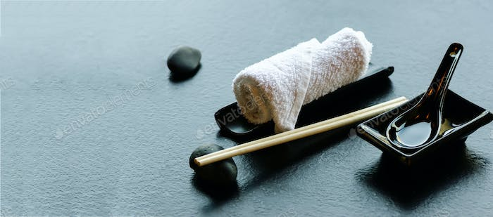 Japanese, asian food utensils - pair of chopsticks, hot weat towel, ceramic black spoon, dark stone