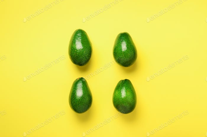 Green avocado pattern on yellow background. Top view. Pop art design, creative summer food concept