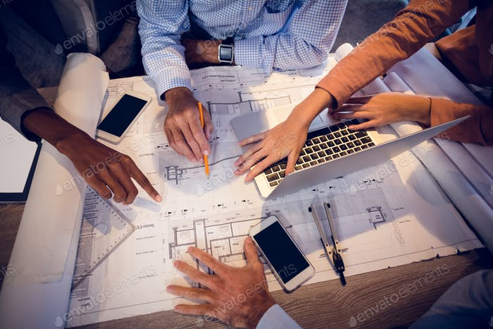 Four architects discussing blueprints in meeting