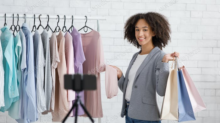 Happy girl with rack with clothes, holds packages in hands, makes video for blog