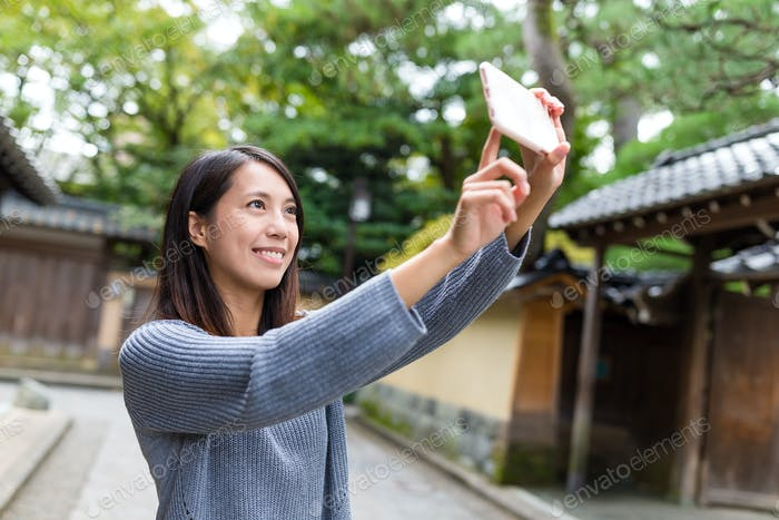 Woman taking selfie photo with mobile phone