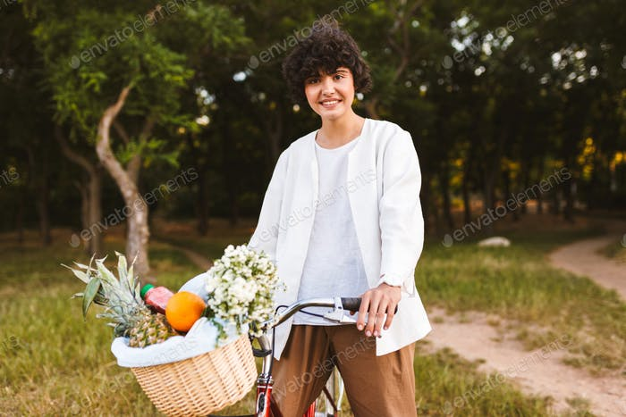 Smiling girl in shirt on classic bicycle and basket full of frui