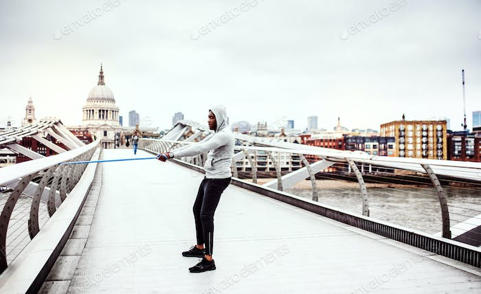 Young active black sportsman exercising with elastic rubber bands in London.
