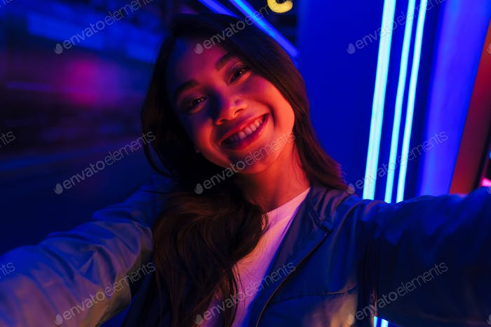 Happy optimistic positive woman posing over neon lights