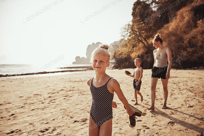 Adorable little girl walking along a beach with her family