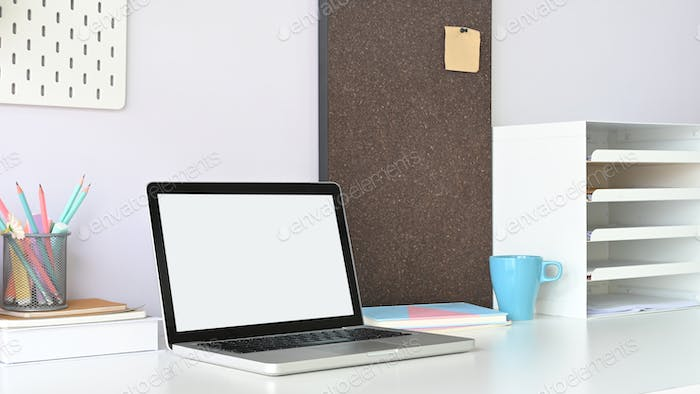 A white blank screen computer laptop is putting on a white working desk.
