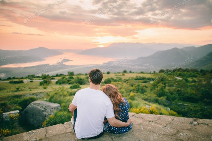 couple relax in mountains at sunset
