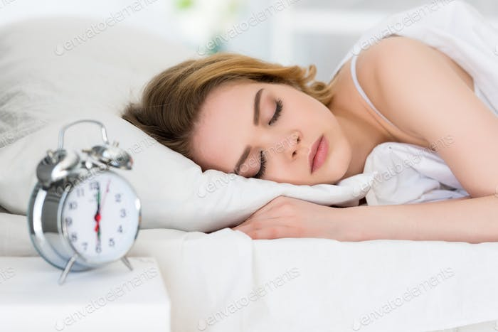 selective focus of young woman sleeping on bed with alarm clock