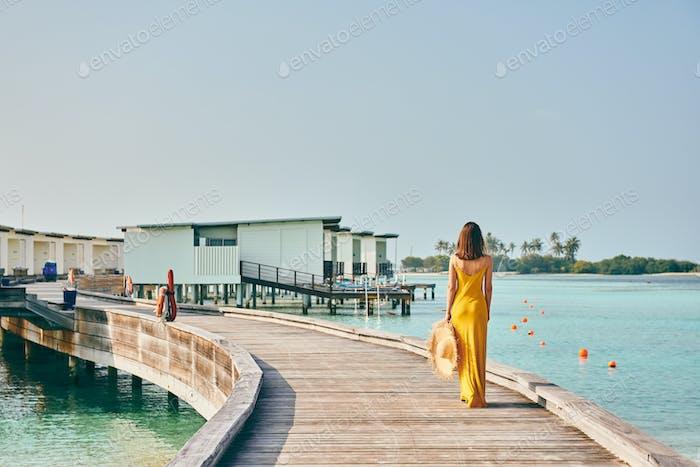 Frau im Kleid zu Fuß auf tropischen Strand Promenade