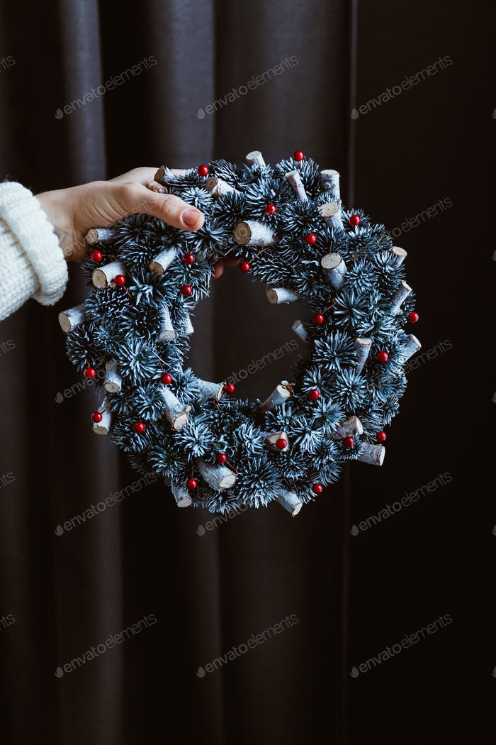 Woman's hand holds a Christmas holiday wreath
