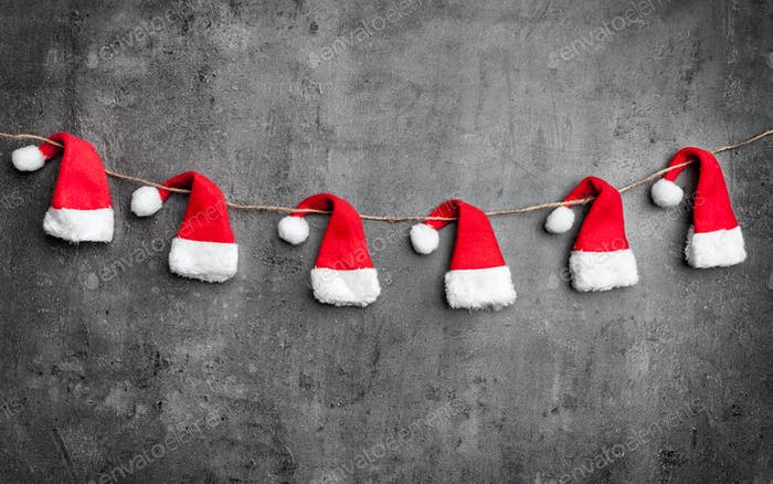Weihnachtsmann-Hüte auf rustikalem Hintergrund mit Kopierraum