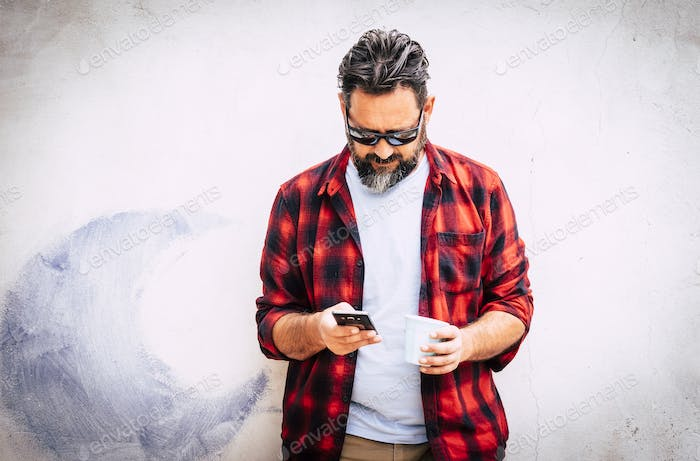 Hipster young caucasian man with beard and red shirt looking at the phone for messages
