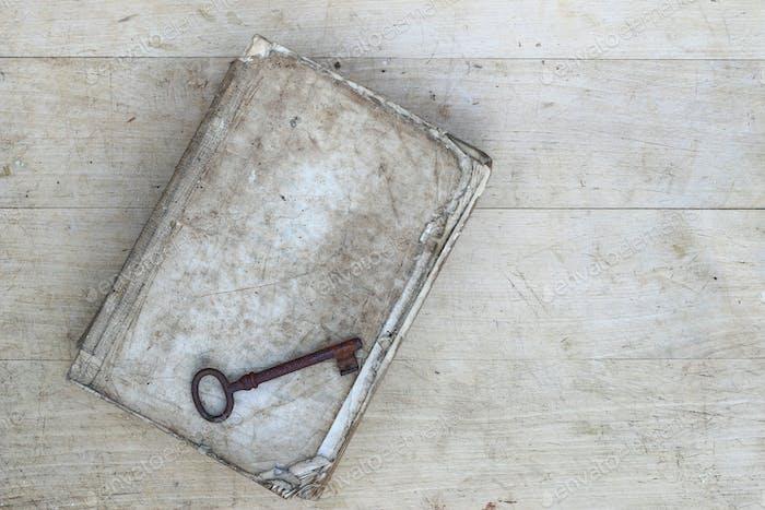 Alte rostige Schlüssel auf zerrissenem Buch