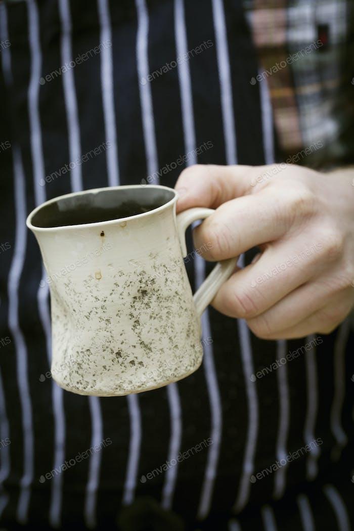 Close up of a chef holding a mug.