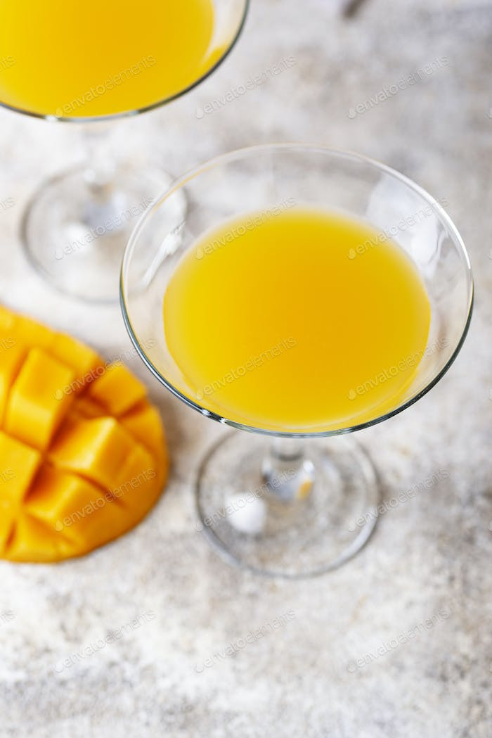 Tropical cocktail with mango on light background