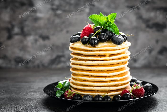 Pancakes with fresh berries. Pancakes with raspberry, blueberry, black currant and honey