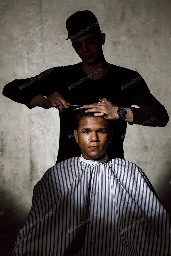 The stylish barber dressed in black clothes scissors the man's hair in a barbershop against a