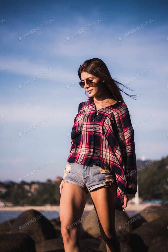 Sexy Girl in flannel shirt on the rocky beach.