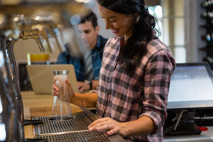 Barmaid preparing drink with customer in background