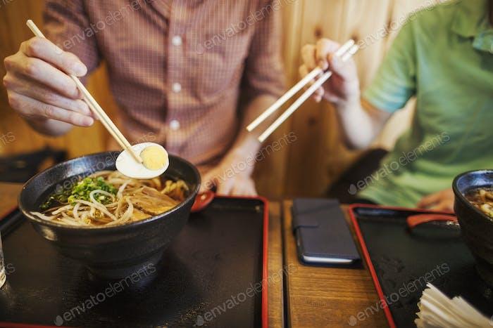 Zwei Personen, ein Japaner, der einem westlichen Mann zeigt, wie man Essstäbchen in einem Nudelladen benutzt.