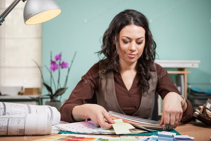 Architect in office picking colors from cards on her desk