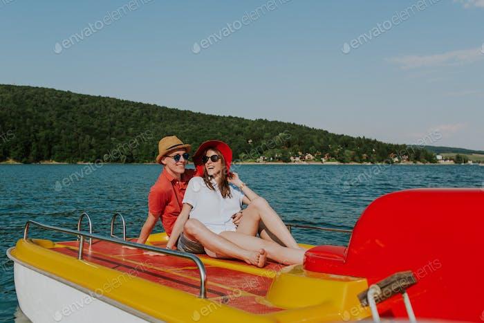 Fröhlicher Mann und Frau, die Spaß beim Bootfahren haben.