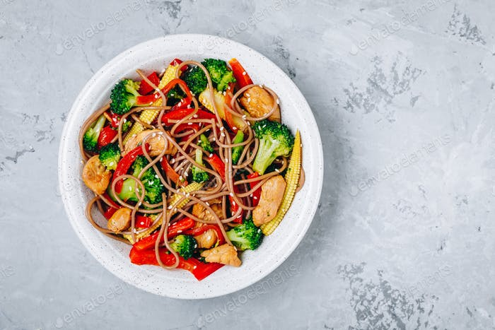 Chicken stir fry noodles bowl with broccoli.