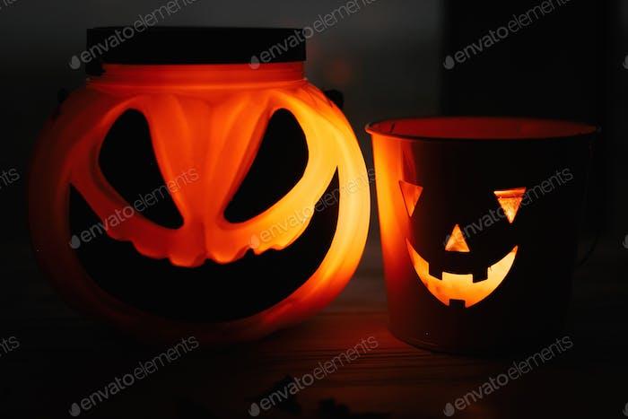 Halloween-Kürbis und Jack o Laterne mit gruselig leuchtendem Gesicht auf schwarzem Hintergrund