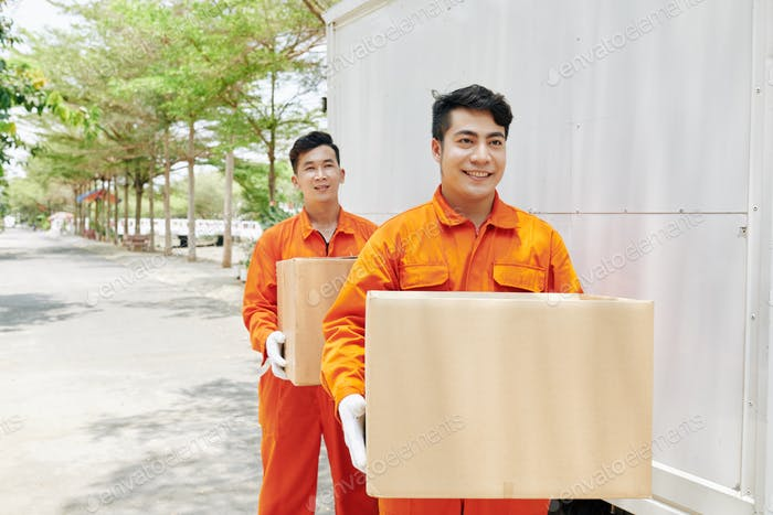 Cheerful Workers Carrying Boxes