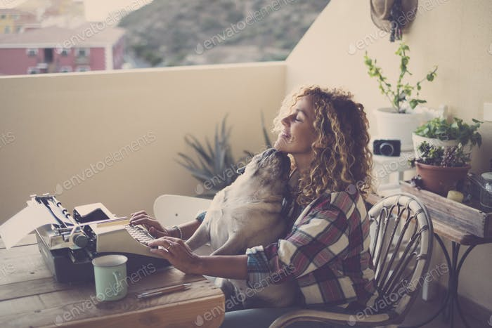 Beautiful middle age caucasian woman use an old vintage typewriter and enjoy the dog