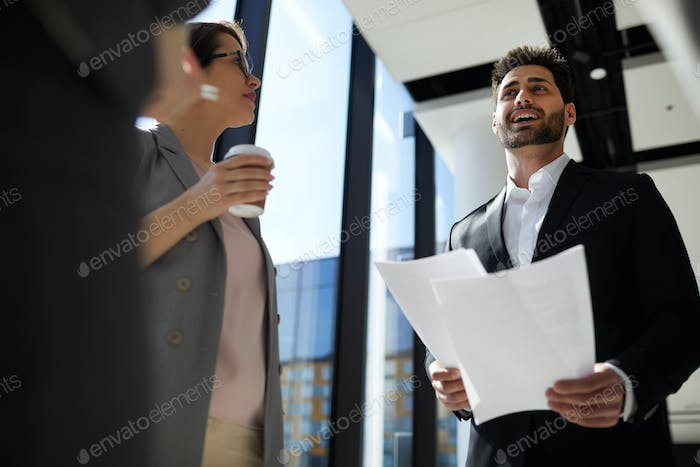 Cheerful businessman reading report with colleagues