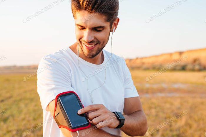 Smiling young sportsman using blank screen mobile phone on armband